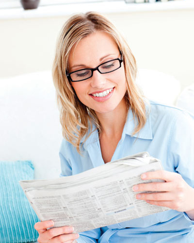 Lady with glasses reading a paper